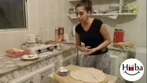 A picture of a kitchen, with Hiba Najem standing behind a table which has a piece of pita bread.