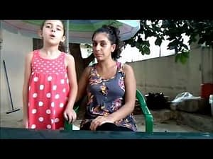 We see Hiba Najem sitting in a garden, and next to her is a standing little girl.