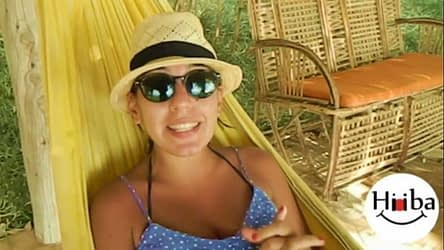 In this image, Hiba Najem is lying on a yellow hammock, wearing a hat and sunglasses